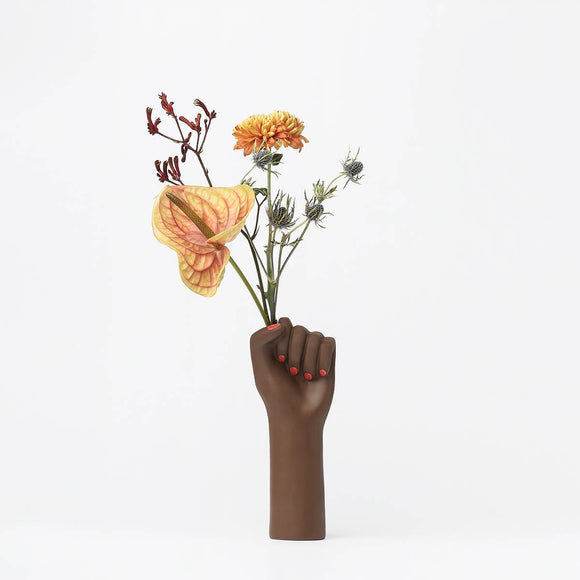 A ceramic vase in the shape of a raised woman's clenched fist. Painted in a matte dark brown coloured glaze and featuring red fingernails. The vase opening is placed in the fists clenched hand, so that it looks like the fist is gripping flowers when in use.