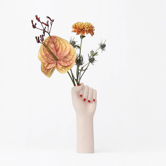 A ceramic vase in the shape of a raised woman's clenched fist. Painted in a matte white skin tone coloured glaze and featuring red fingernails. The vase opening is placed in the fists clenched hand, so that it looks like the fist is gripping flowers when in use.