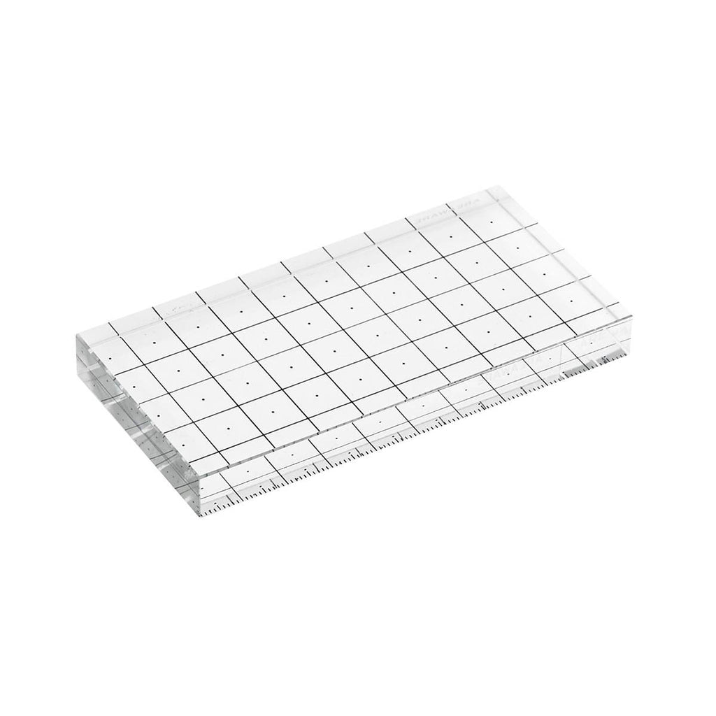 A crystal glass ruler block marked with a 10cm x 5 cm grid.