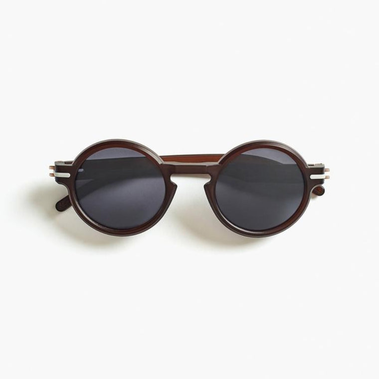 Image featuring a white background with classically designed circular framed  sunglasses in a Cola/Brown  colour