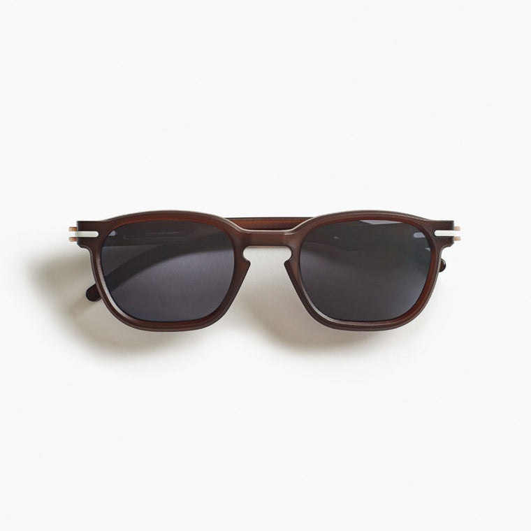 Image featuring a white background with classically designed square framed sunglasses in a cola/brown colour