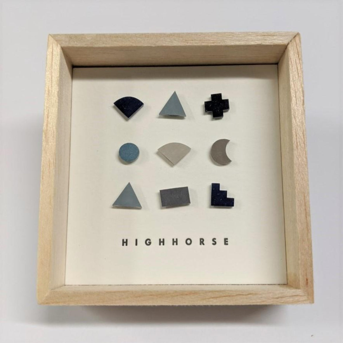 Timber box featuring earring studs including a variety of shapes which include colours of black, navy, light blue, grey and light grey