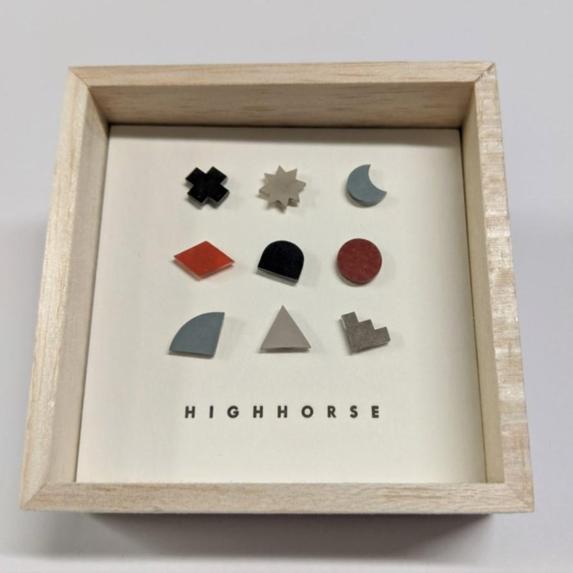Timber box featuring earring studs including a variety of shapes which include colours of dark brown, mushroom, grey, brown and black