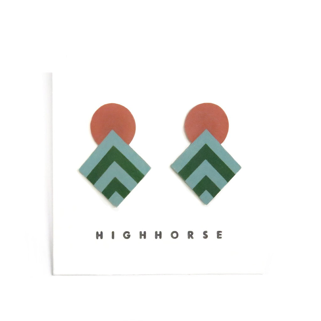 Image featuring a set of two earrings in the center which includes a circle and diamond shape in the colours red, dark green and green - with the words HighHorse on the bottom