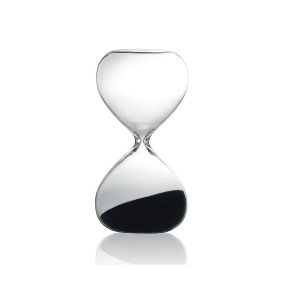 Image featuring a clear glass hourglass in the centre featuring dark sand on the bottom of the hour glass