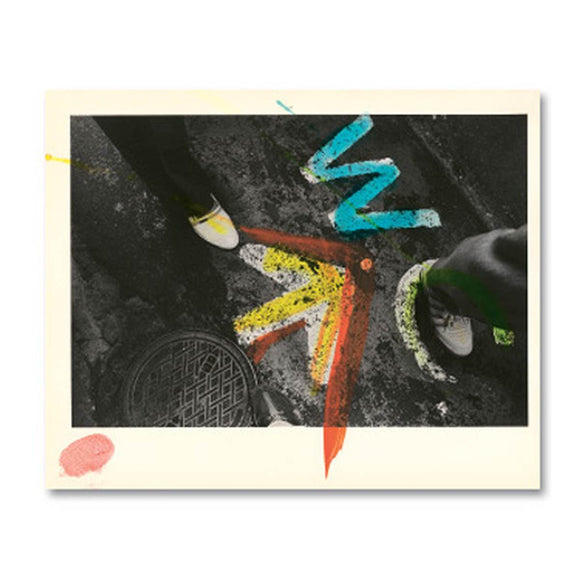 a box of postcards featuring a photo of cracked pavement, adorned with bright free form paint splashes and dots.