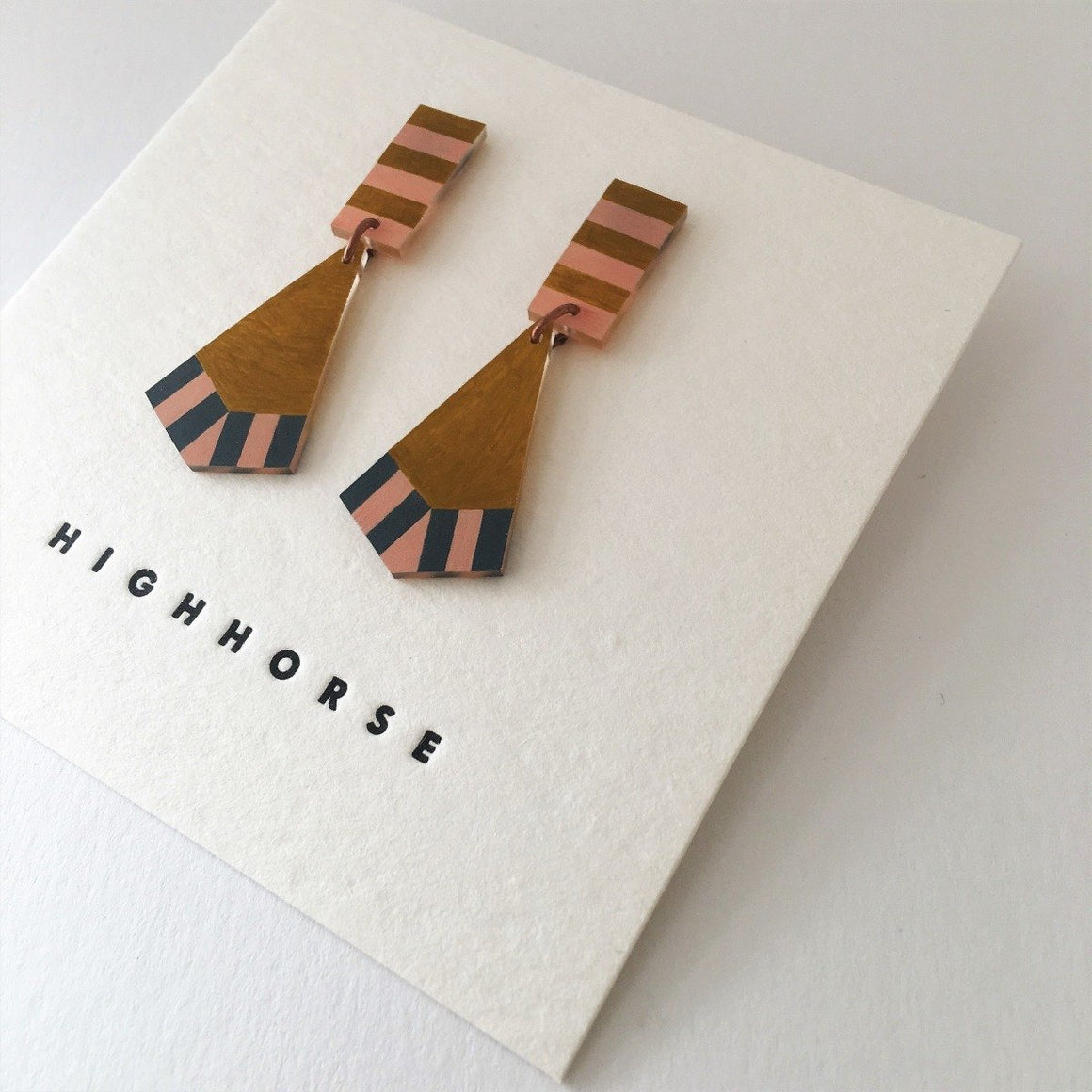 Earrings two featuring a fishtail shape including the colours gold, pink and blue