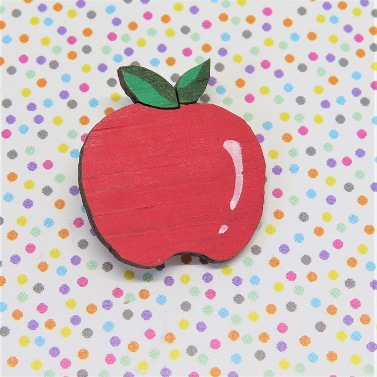 A pin style brooch depicting a rose red apple with green leaves. Made from bamboo wood and hand painted. Shown on a polka dot background.