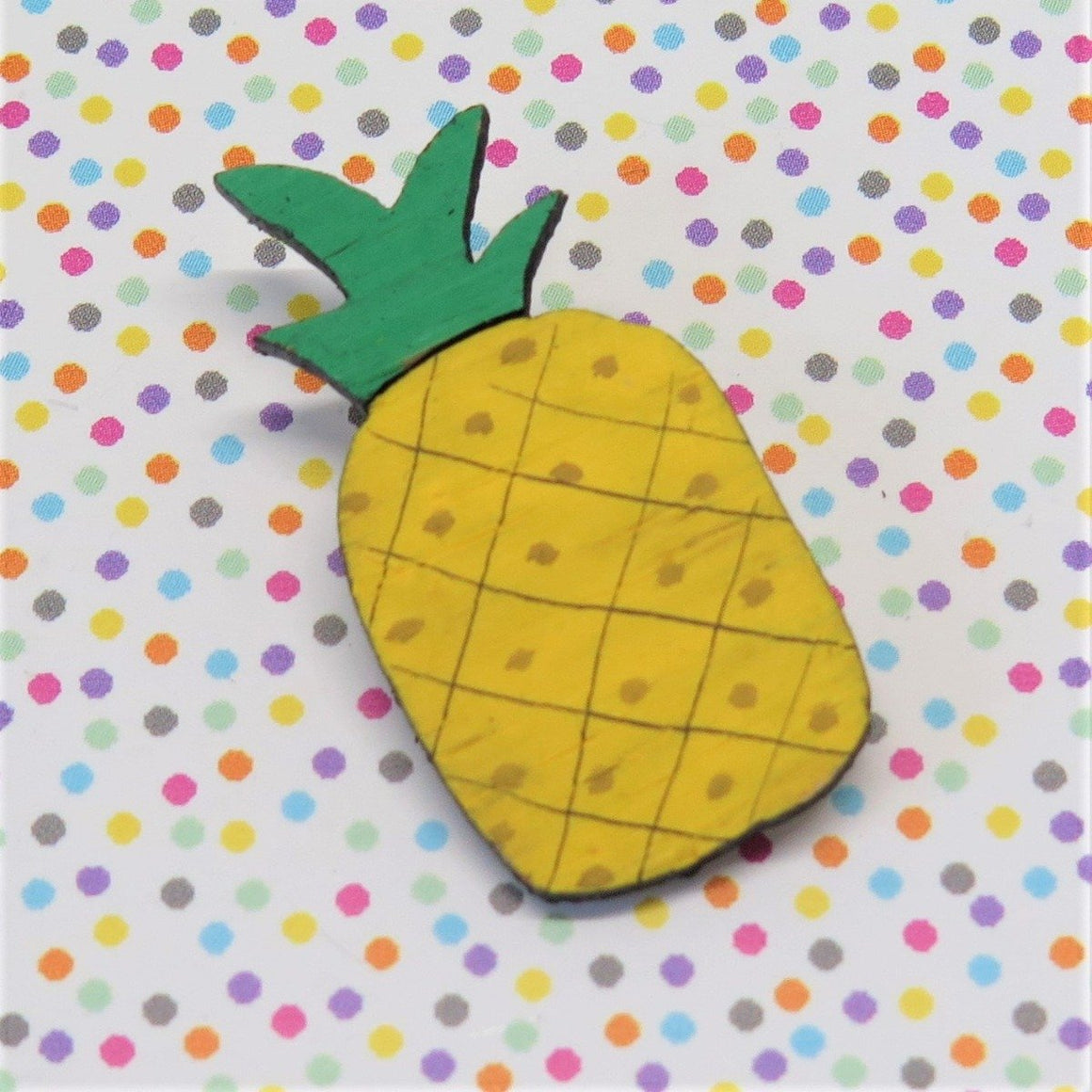 A pin style brooch depicting a bright yellow pineapple with a green stem. Made from bamboo wood and hand painted. Shown on a polka dot background.
