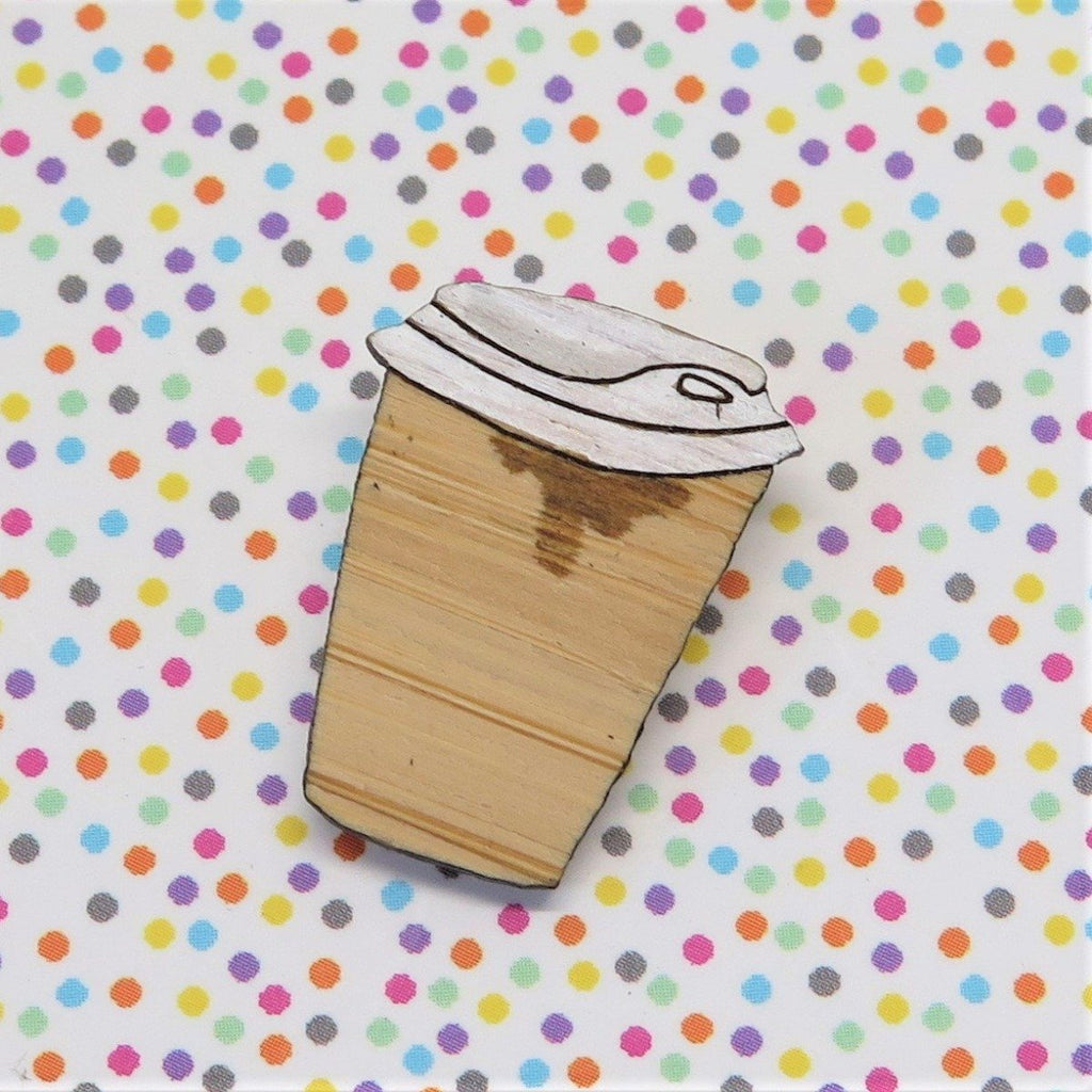 A pin style brooch depicting a takeaway coffee cup with a natural bamboo finish and a white lid. Some coffee has leaked and drips down the cup. Made from bamboo wood and hand painted. Shown on a polka dot background.