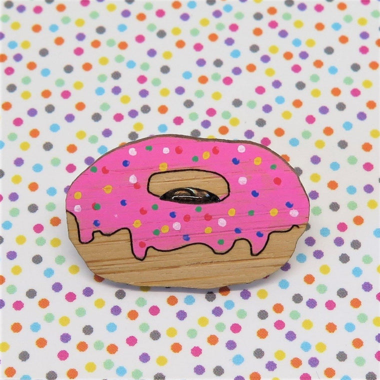 A pin style brooch depicting a pink iced Donut with rainbow sprinkles. Made from bamboo wood and hand painted. Shown on a polka dot background.