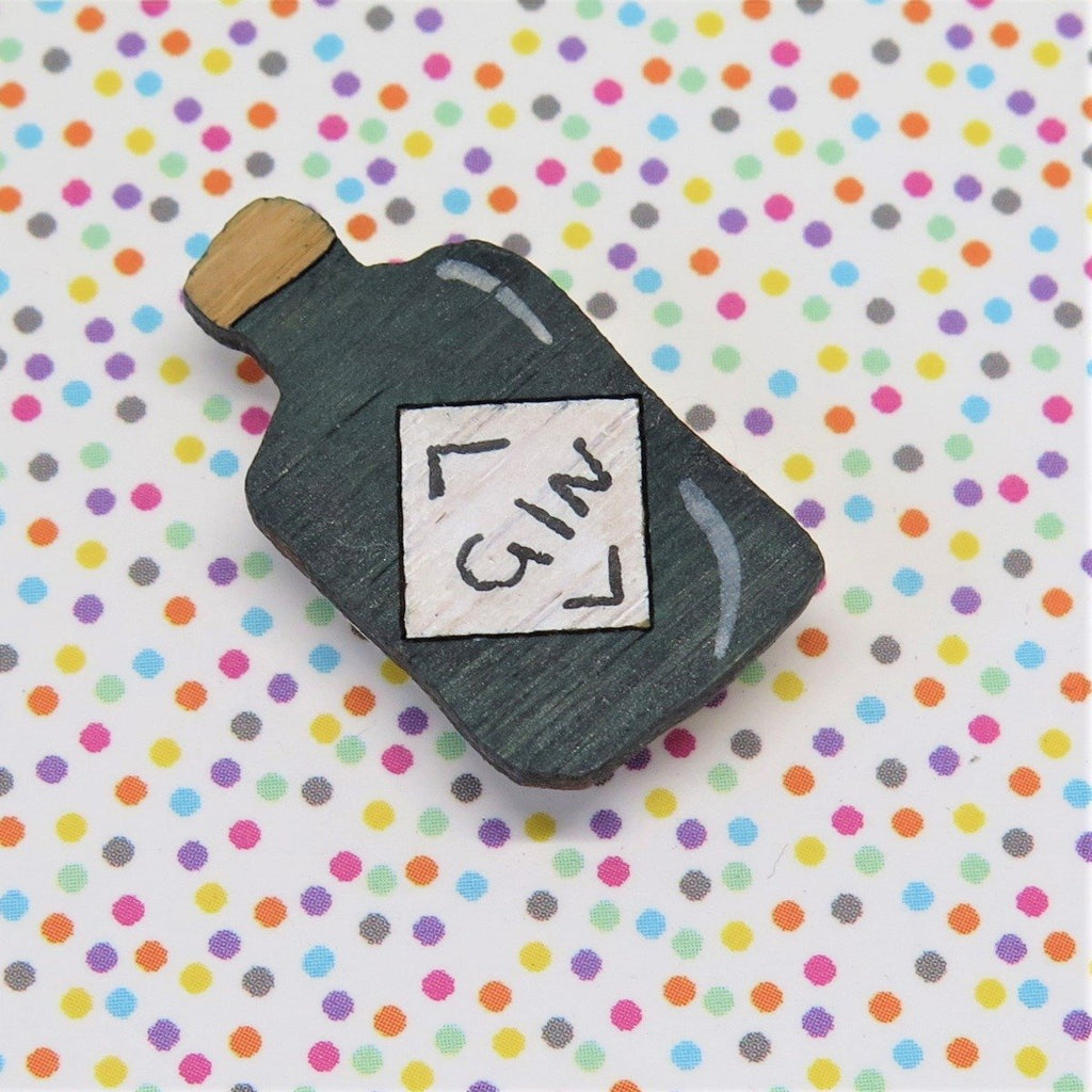 A small Pin style Brooch in the shape of a gin bottle. Displayed on a rainbow polka dot background.