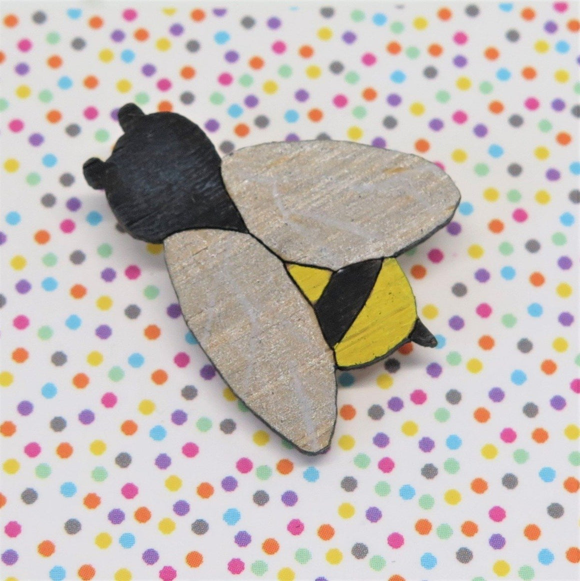 A pin style brooch depicting a yellow and black striped bee. Its wings are painted in variegated silver and white. Made from bamboo wood and hand painted. Shown on a polka dot background.