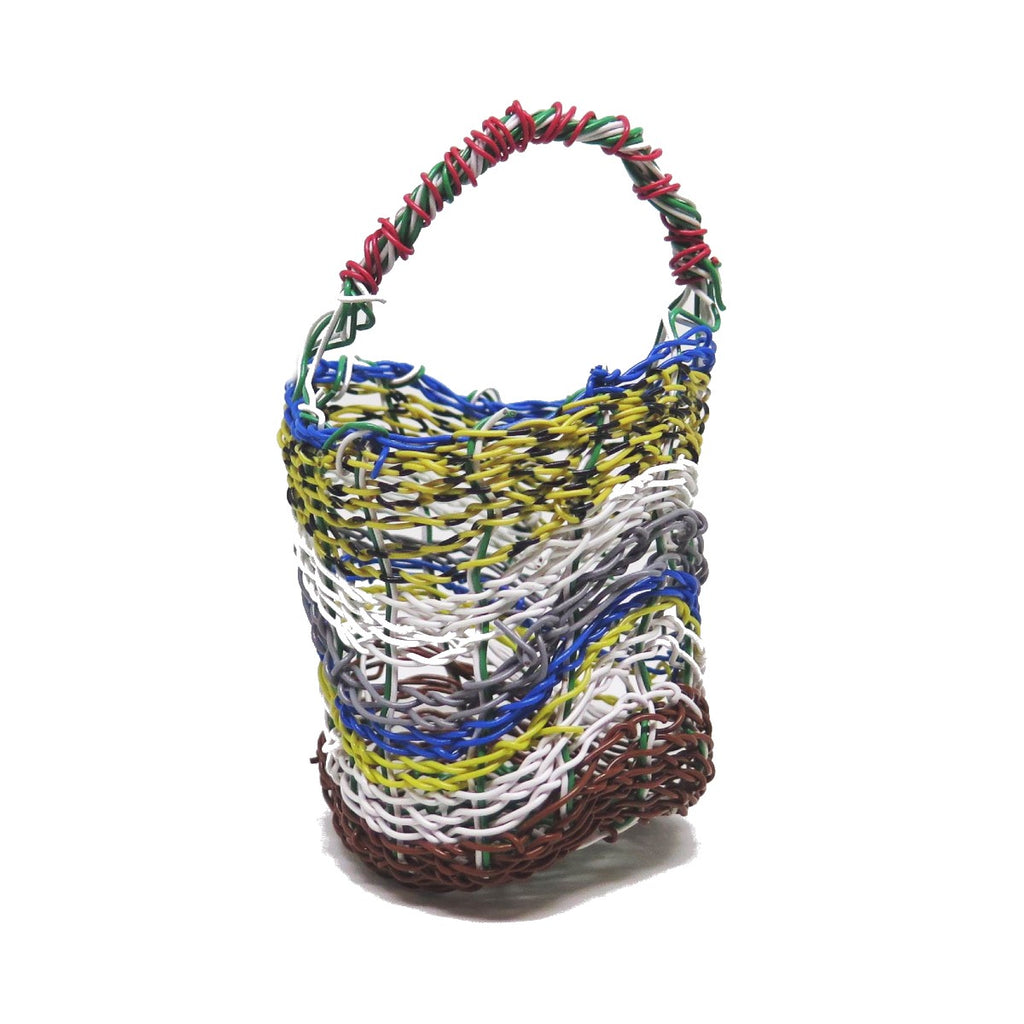 A highly intricate woven 'Mindi' basket created by Aboriginal Artist Debra Murray. It is constructed of woven plastic coated wire in red, white, black, yellow, blue, grey and and green.