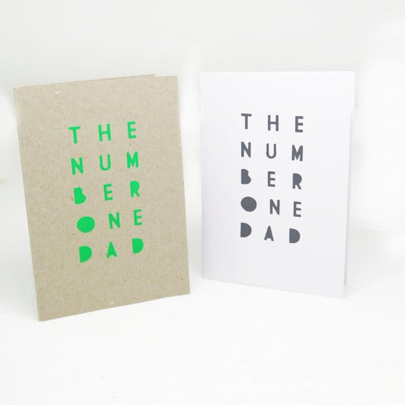 Two Greeting Cards one in white paper and the other in kraft brown paper both which feature the text The Number One Dad in Green and then the other black font