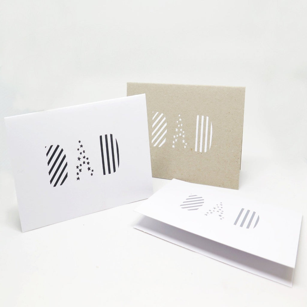 Three Greeting Cards, two in white paper and one in a kraft brown paper all with different coloured font black, white and silver. All feature the word Dad on the front in a pattered font