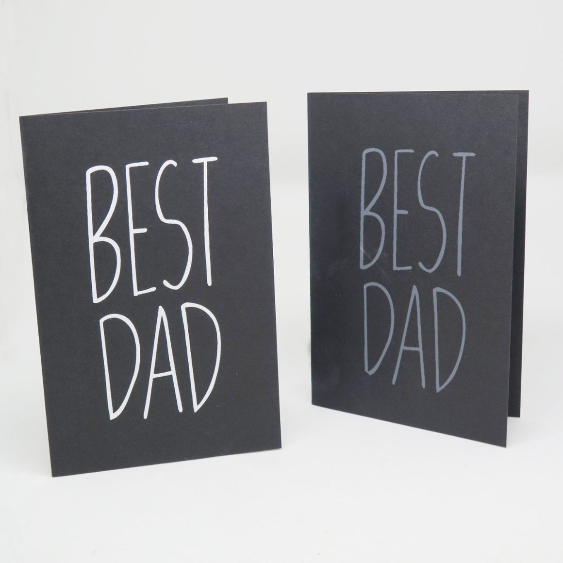 Two black greeting cards featuring simple text stating the Best Dad in white and on the other grey colours
