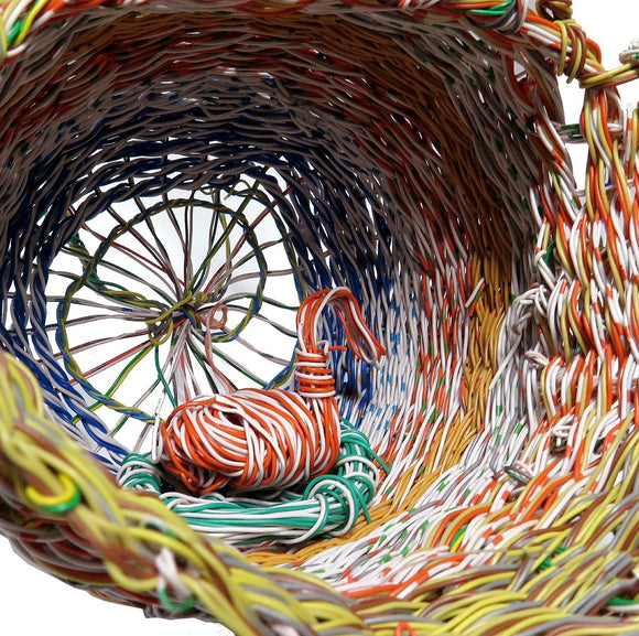 A highly intricate woven 'Mindi' basket created by Aboriginal Artist Emily Murray. It is constructed of woven plastic coated wire in red, white, yellow, orange, blue and green.