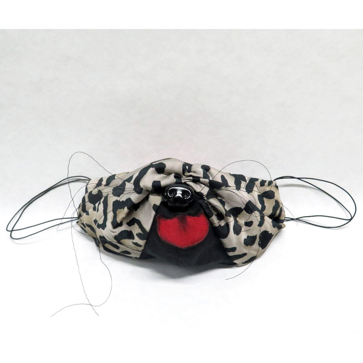 Mask featuring leopard print and black fabric which includes wire whiskers, pink fabric made to look like a tongue and black plastic dog nose