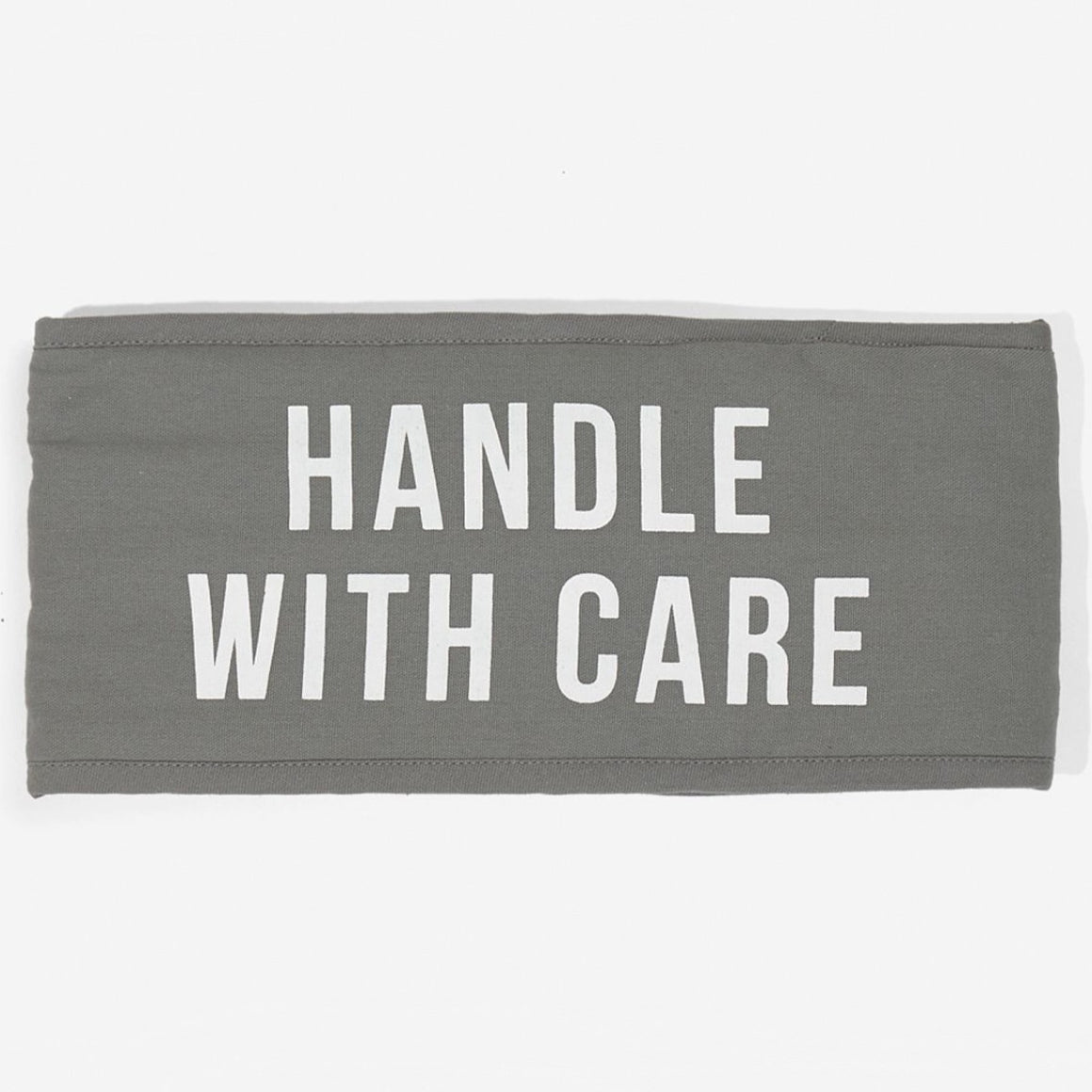 Image featuring a grey square band of fabric (oven mitt folded) with white text on the front saying Handle with care