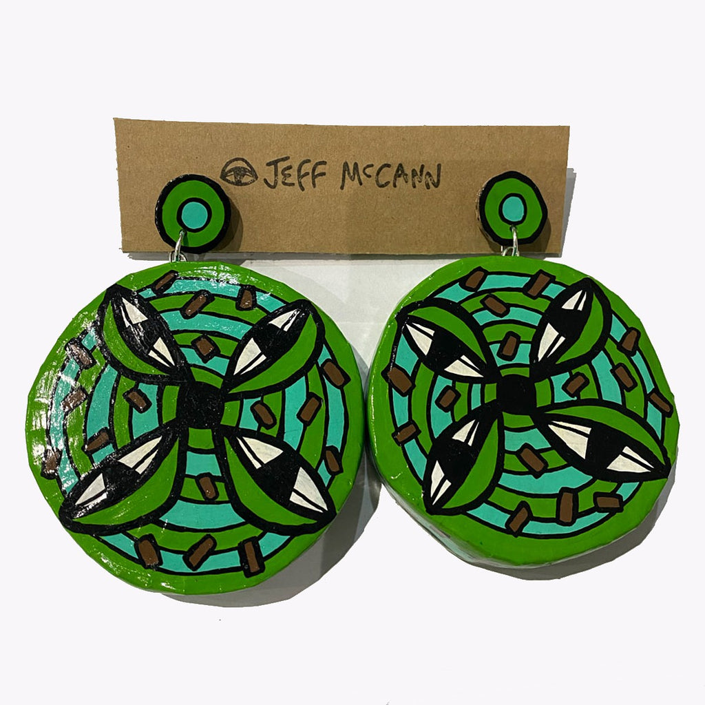 A 3D and sculptural pair of Jeff McCann drop earrings featuring  green discs, eyes and cactus like shapes in green, teal and brown.