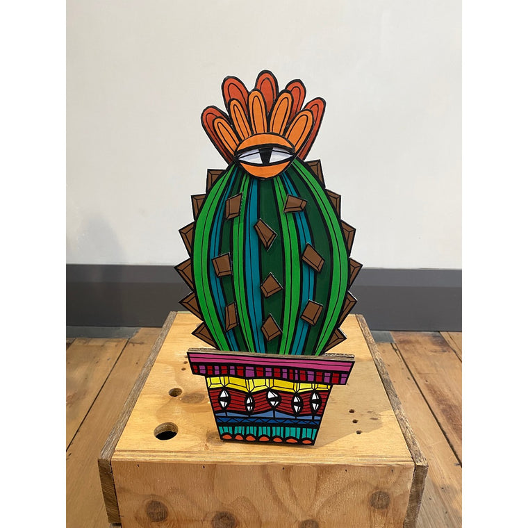 A Jeff McCann Sculpture in the form of a cactus in a pot featuring bright bold colours and patternation and eye motifs. Displayed on a wooden floor in front of a white wall.