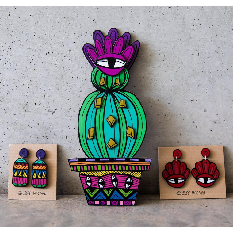 A Jeff McCann Sculpture in the form of a cactus in a pot featuring bright bold colours and patternation and eye motifs. Shown next to two Jeff McCann sets of earring in front of a concrete wall.
