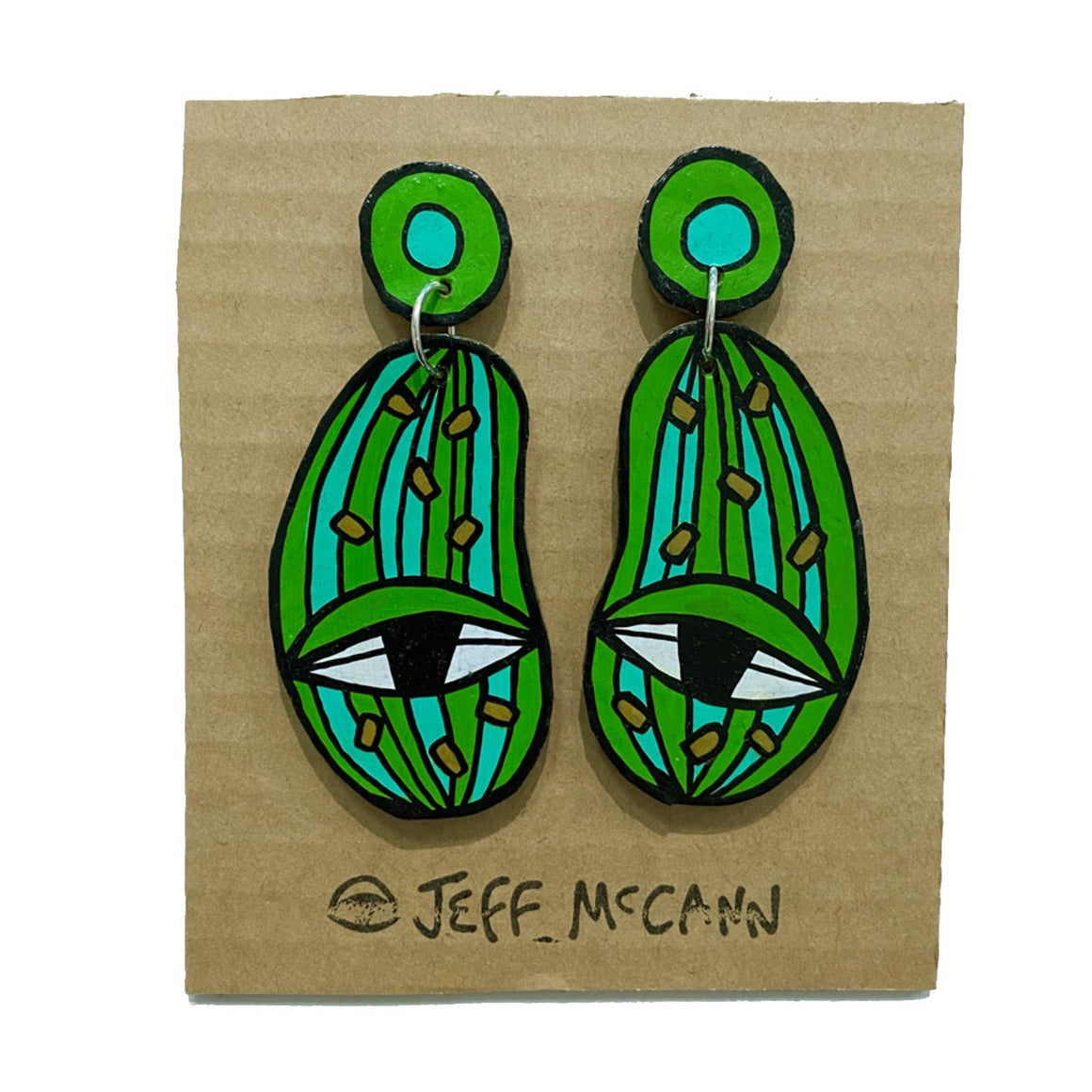 A pair of Jeff McCann drop earrings featuring eyes and cactus and jellybean inspired colours and shapes in green white and black.