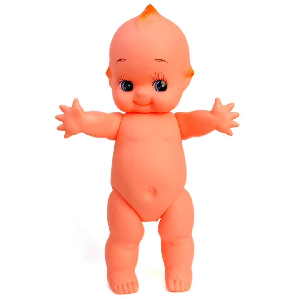 A vintage style Kewpie doll, shown standing with arms upraised. The doll is nude, cherub- like and features large eyes with distinct eyelashes.