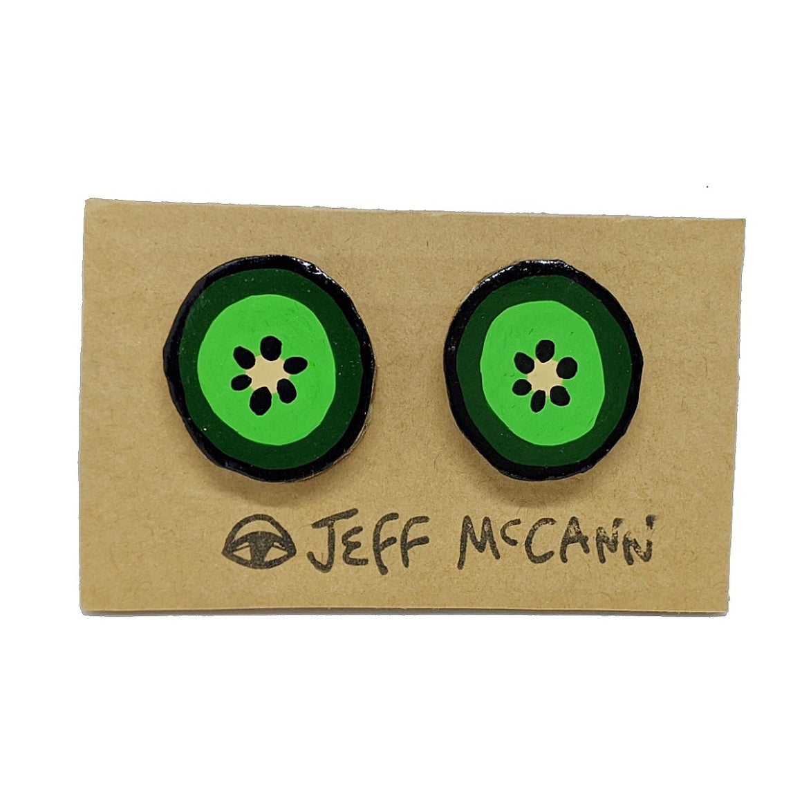 A Pair of stud Earrings made of hand painted cardboard. A design in the shape of a kiwi fruit cut open - in green, yellow and black.