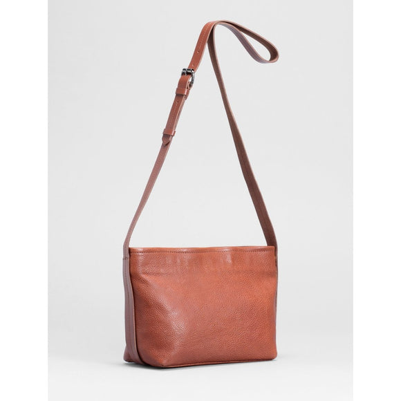 A natural tan leather shoulder bag with a belt style shoulder strap that extends around the sides and bottom of the bag.