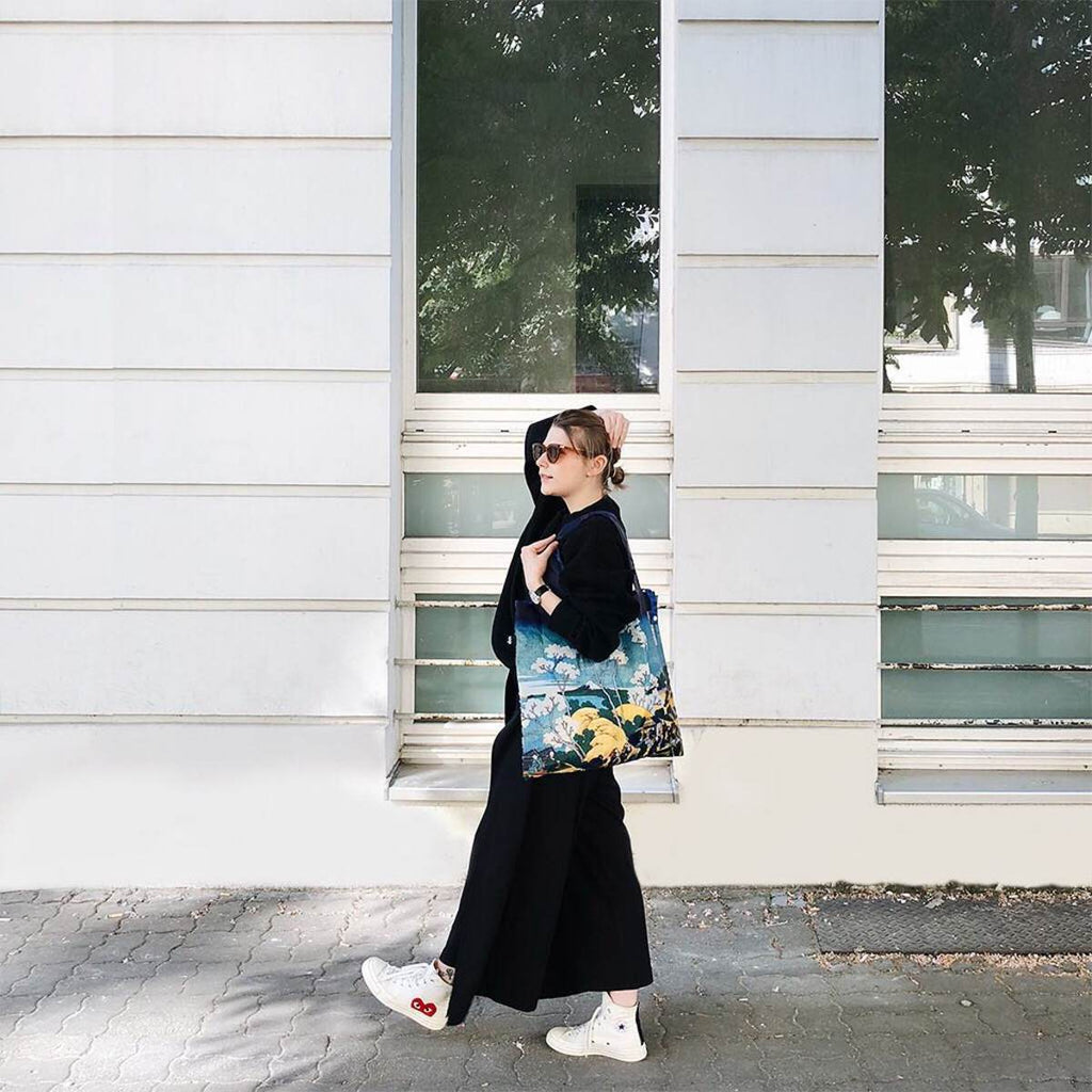 A woman in all black walking down the street next to a white building. She is holding a shopping bag with a Japanese Mt Fuji print