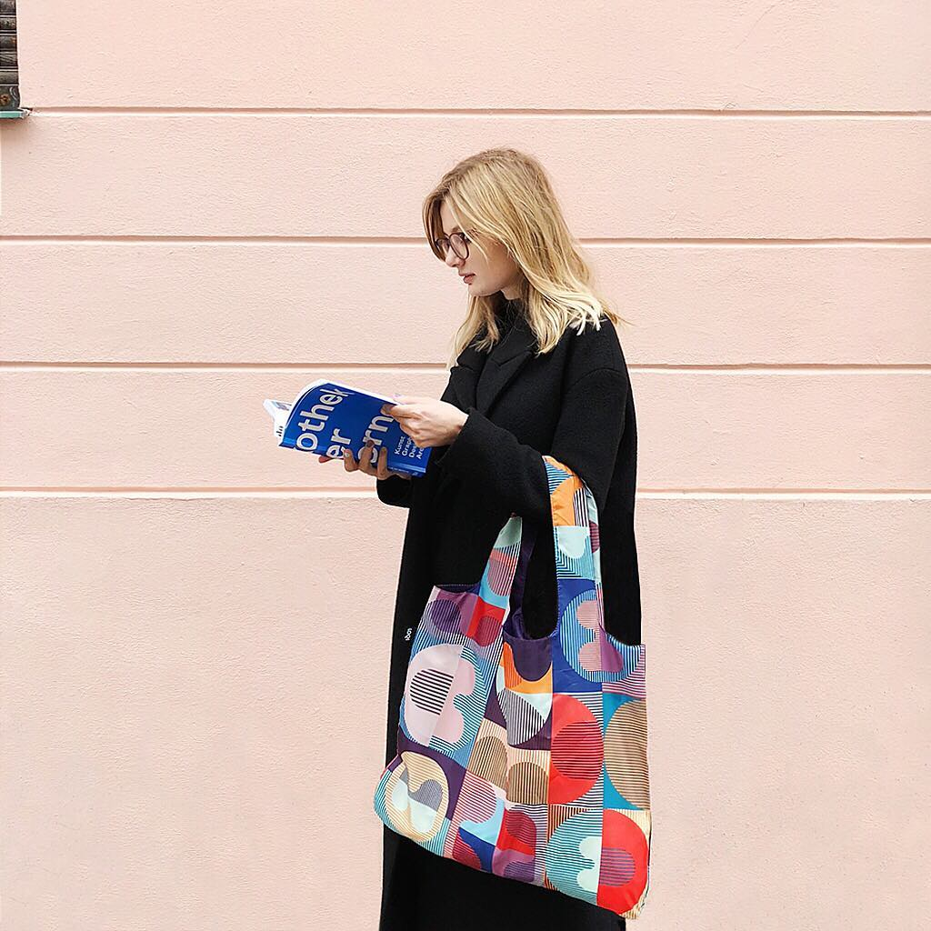 A woman in all black walking down the street reading a blue book. She is holding a shopping bag with a shopping bag with a vibrant geometic print.