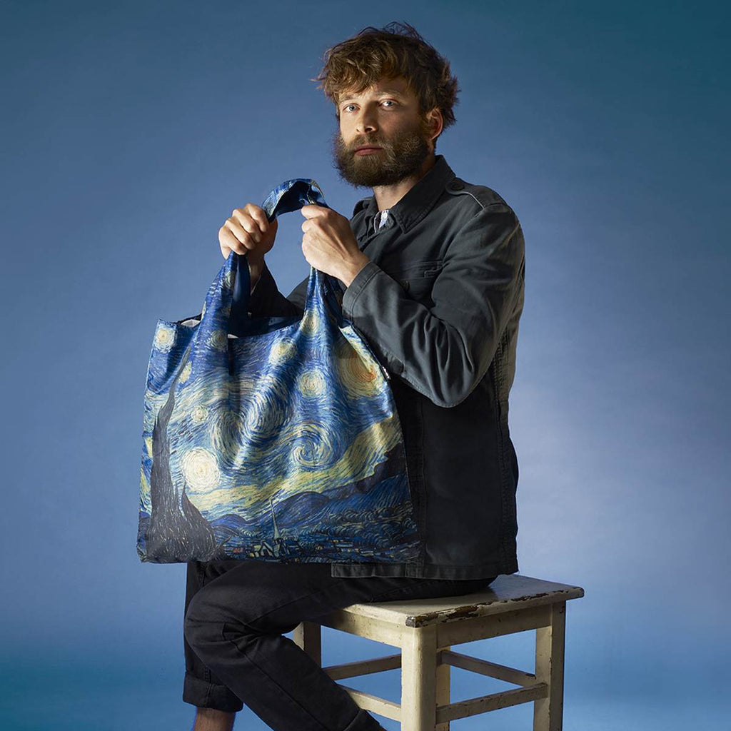 A man impersonating artist Van gogh, sits on a stool. He is holding a shpping bag that features a Starry Night print