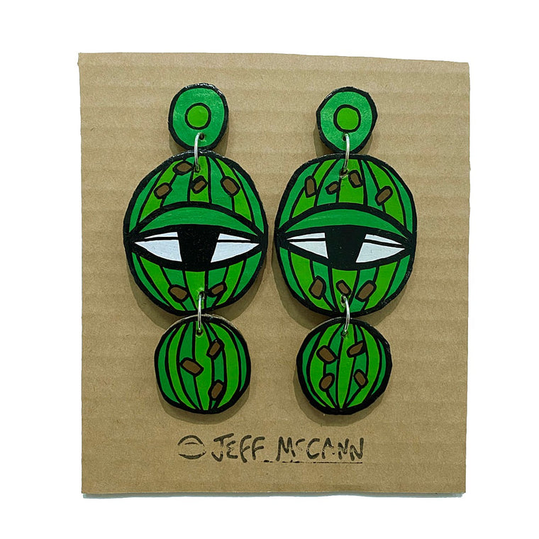 A pair of Jeff McCann drop earrings featuring eyes and cactus and inspired colours and shapes in green white and black.