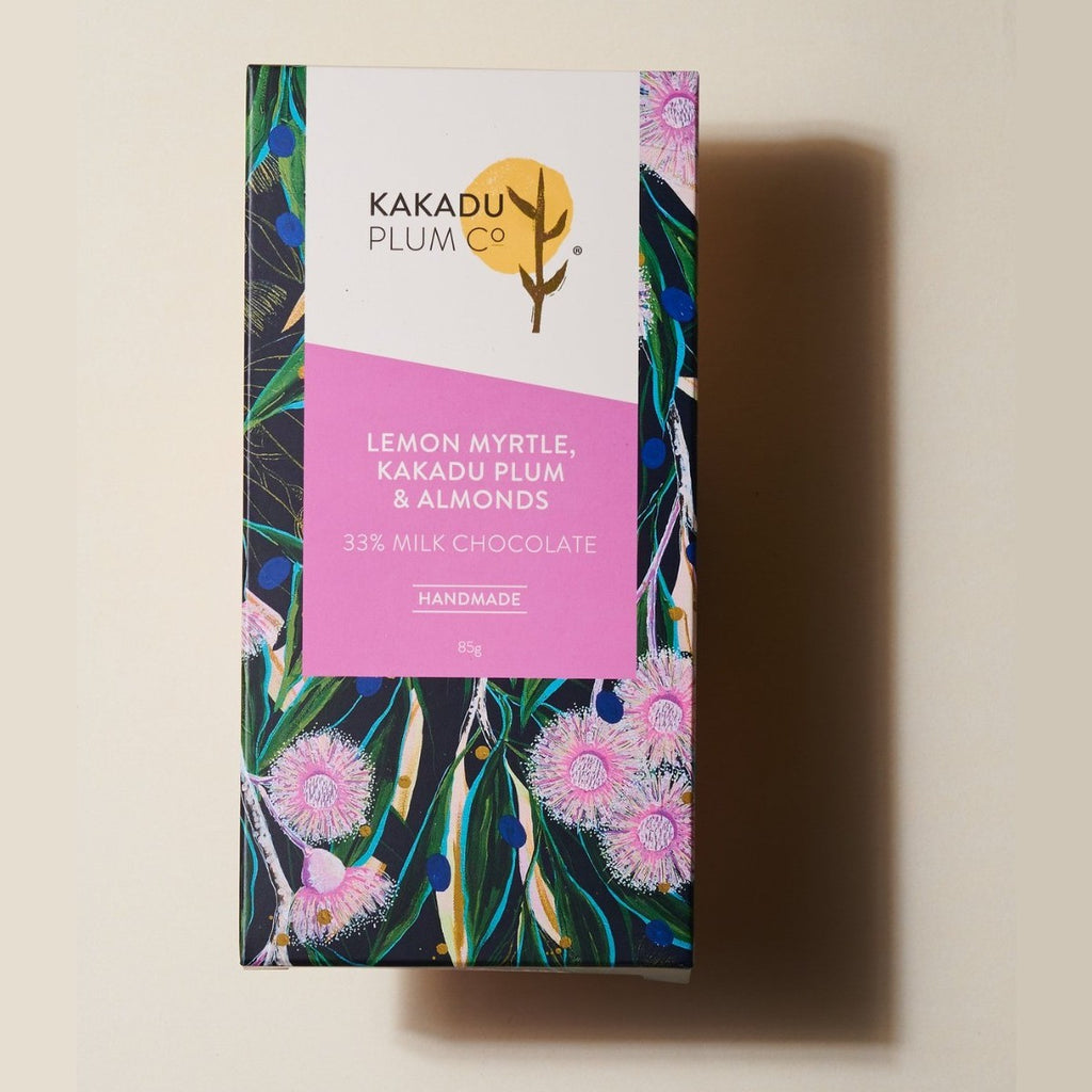A Chocolate bar wrapped in paper with a print of Australian Grevillea blooms and leaves. The Label reads Lemon Myrtle, Kakadu Plum & Almonds, 33% Milk Chocolate, Handmade, 85g
