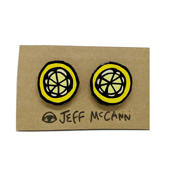A Pair of stud Earrings made of hand painted cardboard. A design in the shape of a kiwi fruit cut open - in yellow tones and black
