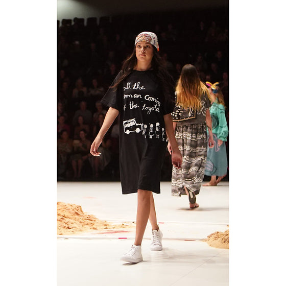 "A young indigenous model, walks the runway wearing a black t-shirt dress. The dress is printed with an artwork by Sally M Mulda in white depicting women standing next to a 4 wheel drive, and the text ""All the woman coming in the toyota"""