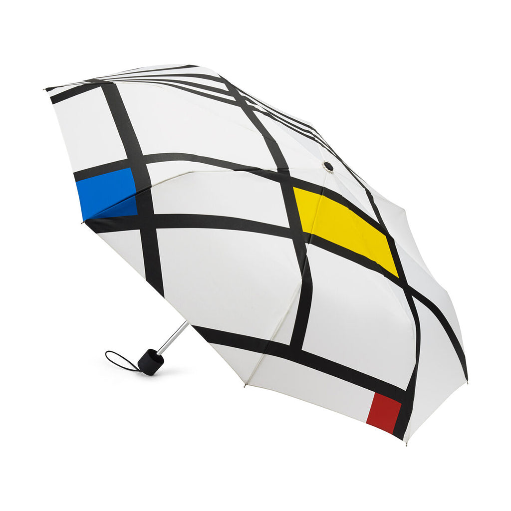 a Compact umbrella is shown open and resting on its side. It is adorned with a block colour graphic inspired by the work of Piet Mondrian.
