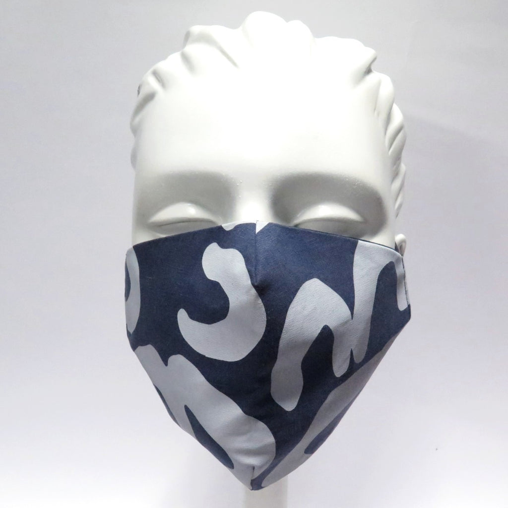 A mannequin is shown wearing a face mask made from fabric designed by artist Mavis Masks. The fabric consists of white shapes on a deep blue base.