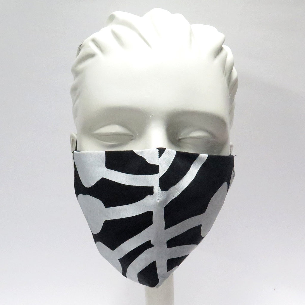 A mannequin is shown wearing a face mask made from fabric designed by artist Kumuntjai Napurrula. The fabric consists of white tree motifs on a black base