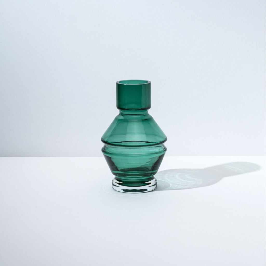 A structural and ridged glass vase in a deep green tone