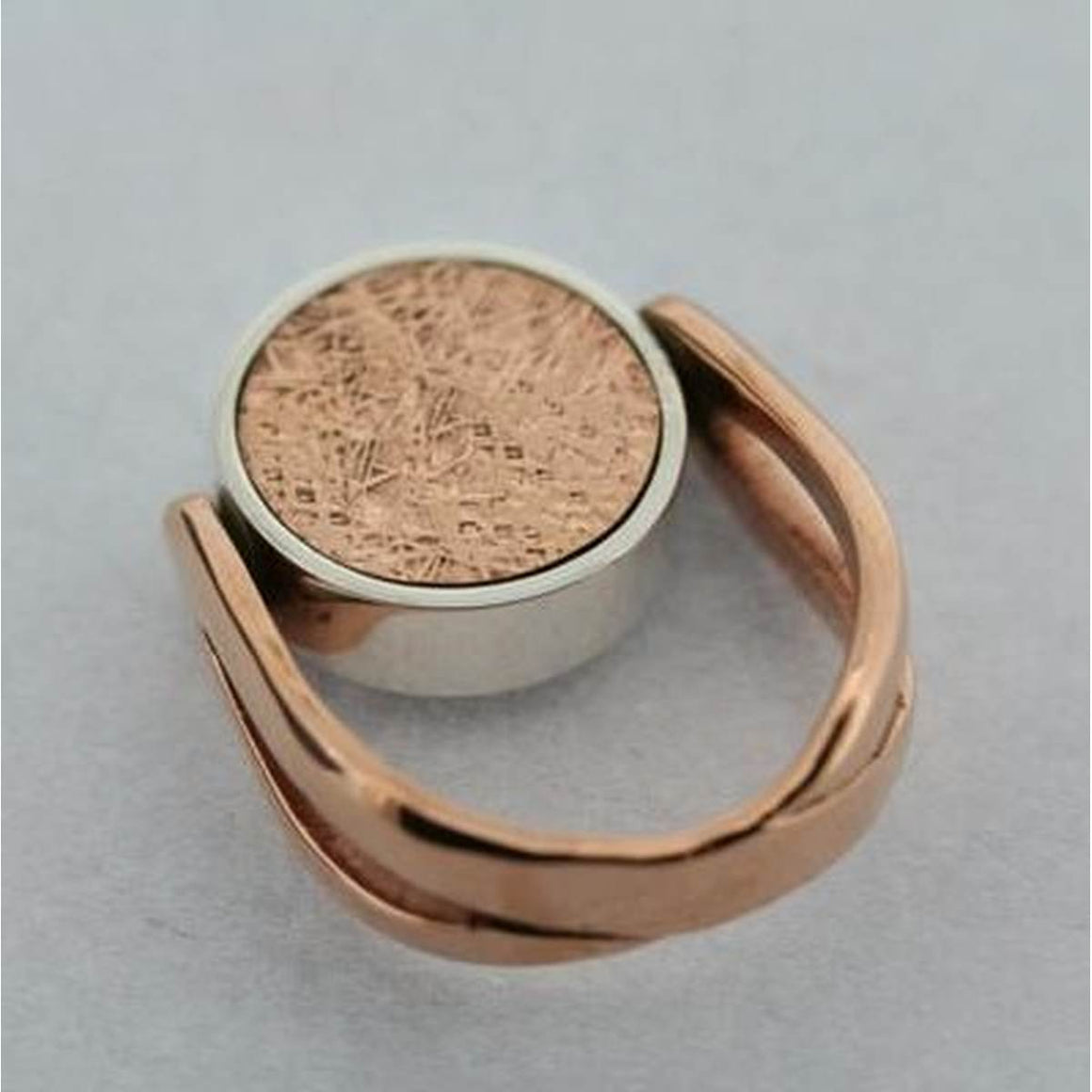 An unusual and sculptural Copper coloured ring. Featuring a spinnable disc which has a textured copper on one side and a Black Obsidian stone on the other.