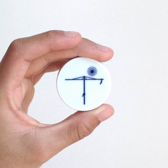 A circular disc shaped porcelain magnet with a blue and white cobalt oxide glaze design on it. The design is a stylised version of a Hills Hoist washing line. The magnet is shown in its stylish square translucent gift box.