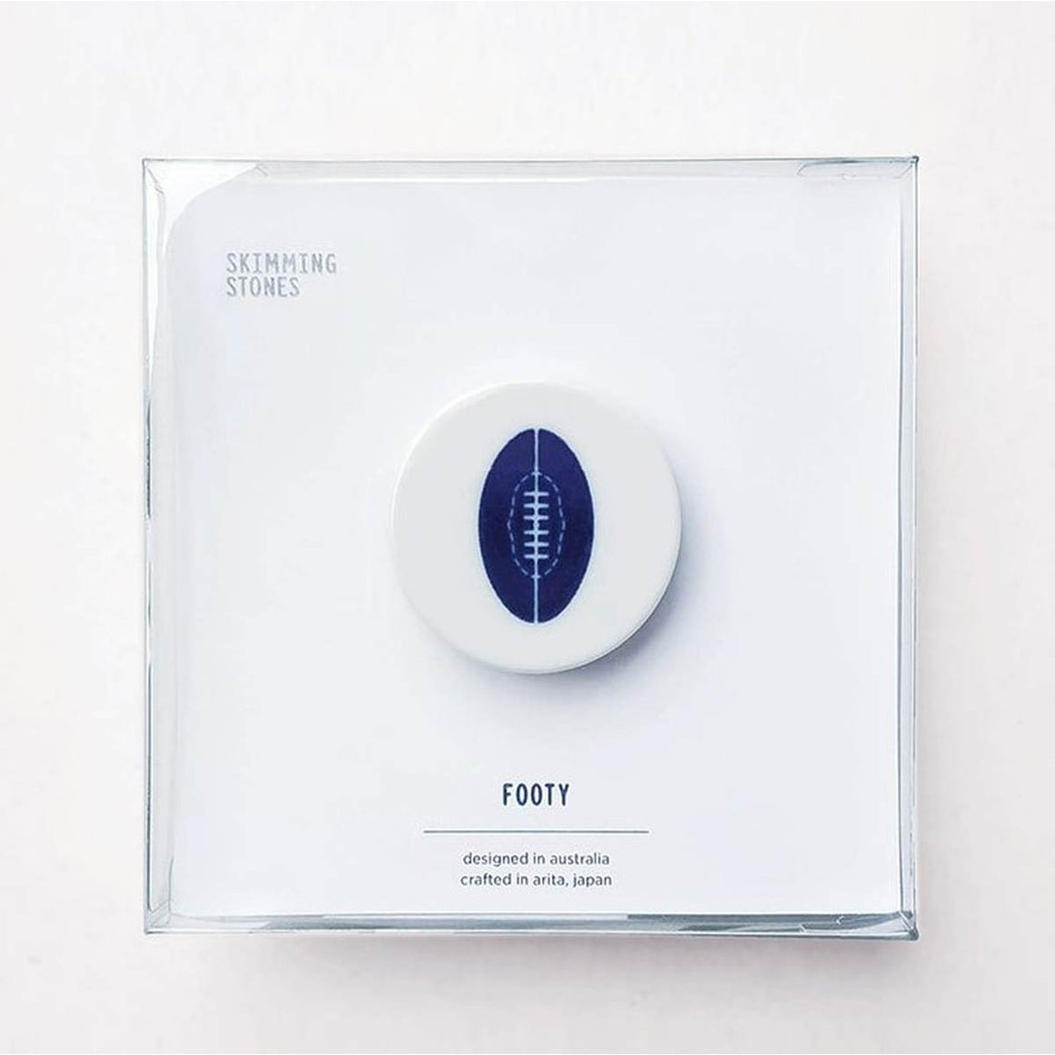 A circular disc shaped porcelain magnet with a blue and white cobalt oxide glaze design on it. The design is a stylised version of an Australian Rules football. The magnet is shown in its stylish square translucent gift box.