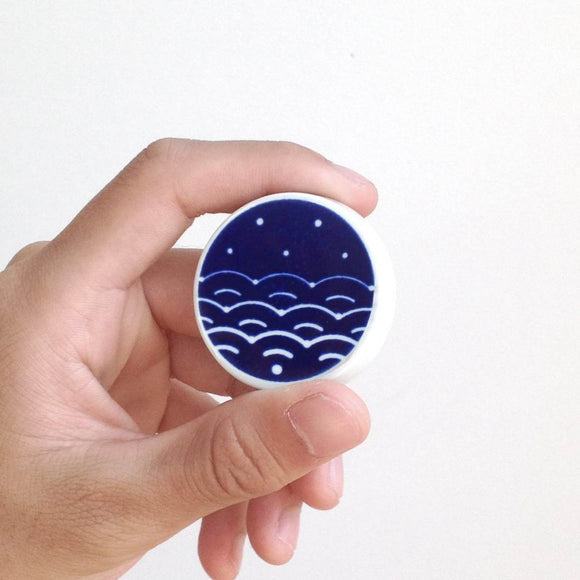 A circular disc shaped porcelain magnet with a blue and white cobalt oxide glaze design on it. The design is a stylised abstract which mimics traditional japanese patterning while incorporating the WiFi symbol. The magnet is shown in its stylish square translucent gift box.