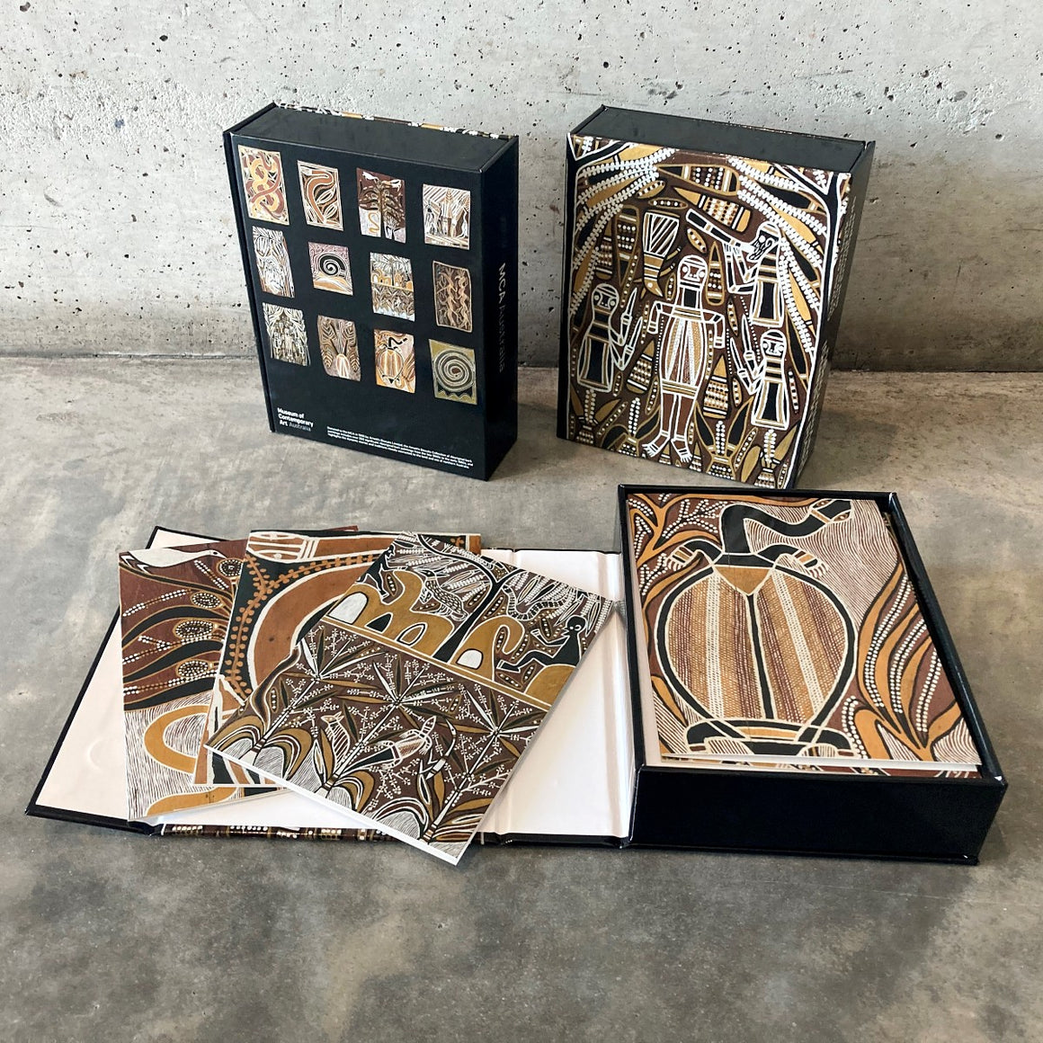 The front and back of a card set containging 12 cards printed with the ochre on bark works by David Malangi Daymirringu. In the foreground one card set is open displaying four card designs.