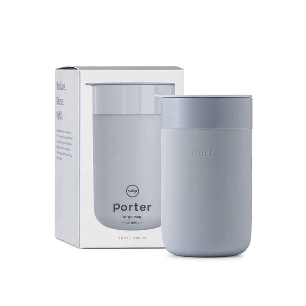 "A slate grey travel mug composed of Ceramic and Silicone. Shown in front of its box which features the text "" Port to-go mug"" and "" Reduce, Reuse, Refill""."