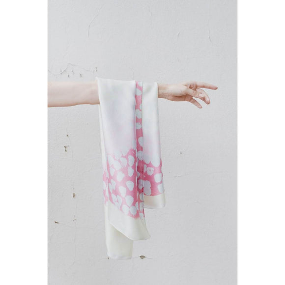 a Silk scarf , printed with an abstract Aboriginal artwork. Subtle pastle tones of pink, purple, cream and white are used to create a circular negative space in the centre of the scarf.