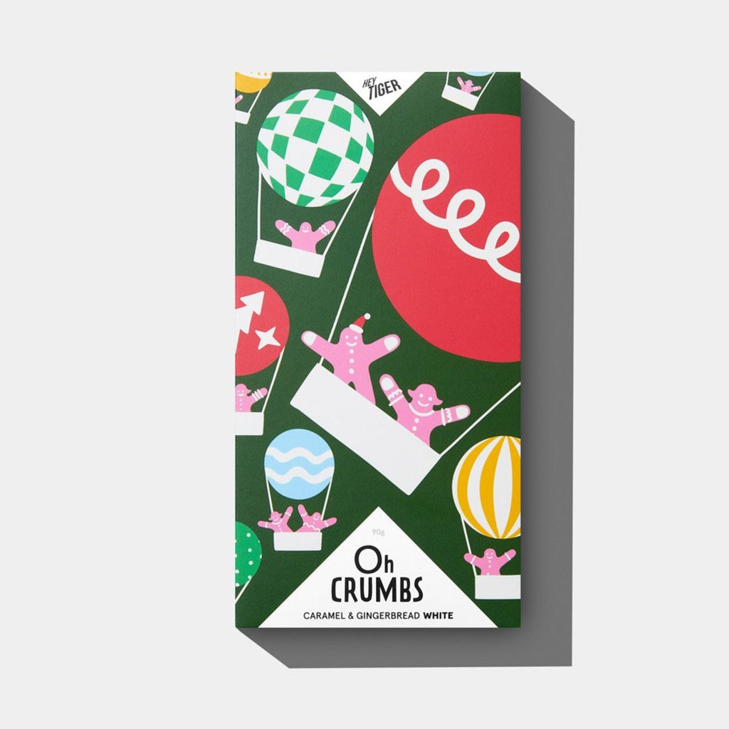 A block of chocolate. The packaging features gingerbread mean floating in brightly coloured hot air balloons on a deep green background.